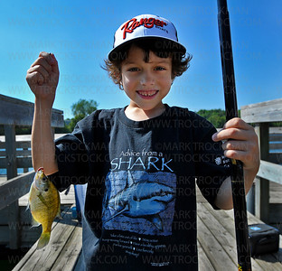 Keelin Samson-Garry, 7, holds a sunfish he caught off of the fishing pier on Shady Oak Lake in Minnetonka Wednesday, July 11, 2012.  Keelin joined dozens of young anglers for the Laun E. Anderson Kids Fishing Contest as part of the myriad of activities for young and old celebrating the annual Hopkins Raspberry Festival.