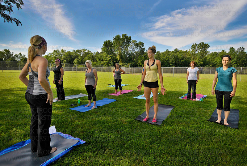 "Freeman Park in Shorewood played host to Holy Yoga, led by instructor Pamela Helling, left, Friday, July 29.  Another Holy Yoga instructor, Bethany Connely, in yellow top, says, ""It's a blessing to do yoga outside in nature."""