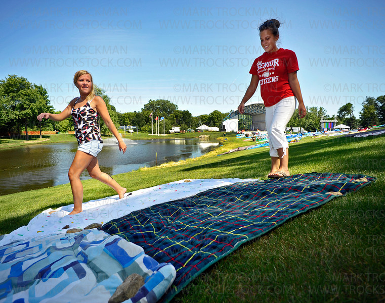 Recent Wayzata graduates and friends Britta Swanson, left, and Maddie Berglund spread rocks they pulled from the pond area to weigh down their blankets.  Tent stakes were not allowed this year to help keep large swaths of plastic and cotton blankets in place.  Staking out real estate at the Amphitheater is a big deal and folks were faced with new rules regarding when, how and where to snag their patch of grass.
