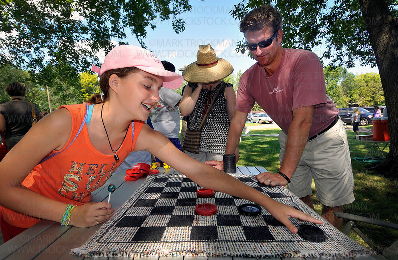 An gargantuan game of checkers is played by Anna Serino, 11, and David Quinn at Corn Days in Long Lake Saturday, Aug. 14, 2010, at the Church of St. George.