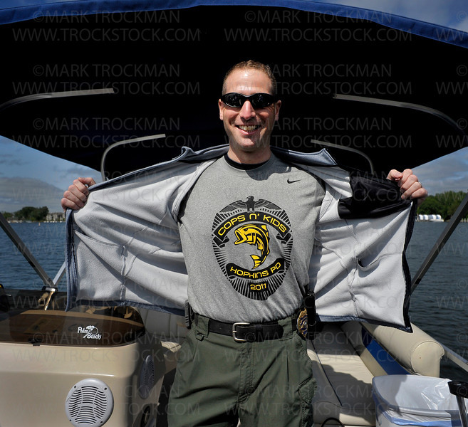 Hopkins Police sergeant Michael Glassberg shows off his Cops n' Kids t-shirt aboard a rental boat on St. Albans Bay on Lake Minnetonka in Excelsior Thursday, June 9.  Sgt. Glassberg was one of several Hopkins Police officers and employees that accompanied about two dozen Hopkins School children from under privileged living situations for the free, day-long boating and fishing event.