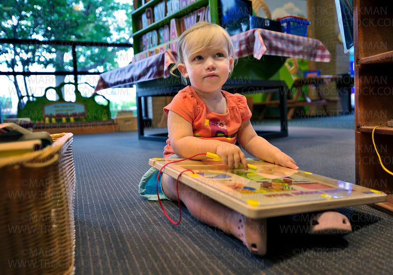 Elza Schmerler, 22 months, plays with a magnetic shapes maze on the floor of the children's section of the Hopkins Library. The library was crowded with folks attending, 'Happy 100th: Then, Today, Tomorrow': A celebration of the Hopkins Library's 100th birthday with tales of the Dow House and ghosts, photo displays, contests and local authors Sunday, June 03, 2012.