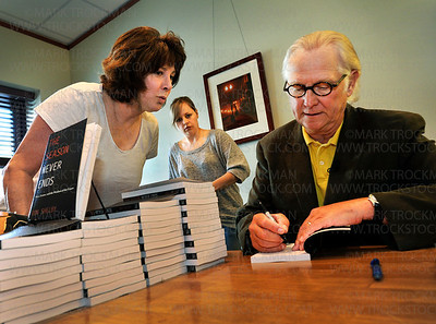 New author Don Shelby, right, signs his book, The Season Never Ends, for Nancy Williams, left, Shoreview.  Williams bought four books.  Ashley Shelby, Mr. Shelby's daughter, center, accompanied her father and spoke to the gathering at the Excelsior Dunn Bros.