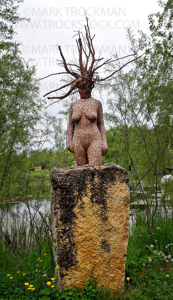 This stone and wood piece, Earth Mother, watches over mini golf players on the 12th hole, a Par 2 called Pachinko at Big Stone Mini Golf & Sculpture Gardens in Minnetrista.