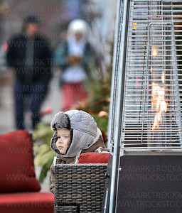 Lola Werner, 2, from St. Louis Park, stays warm out side the Marquee Building in downtown Wayzata by sitting next to a contemporary outdoor flame on Lake St. E., while her grandma, Diane Johnson, kept watch during Wayzata's Holiday kickoff Friday, Nov. 30.