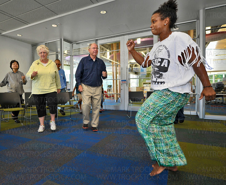 Kenna Cottman, right, teaches a dance to participants Rick and Barb Whiting, Plymouth, in blue and yellow, and others during 'Global Folk: West African Drum and Dance' program Saturday, Sept. 15, at the Plymouth Library.  <br /> <br /> Cottman, and her son and daughter hosted this interactive program which included drumming, dancing, rhythm-making, and singing, free of charge.