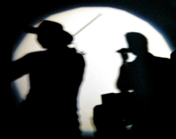 Shadows in the spotlight.  Emerson Drive's David Pichette on fiddle (left) and lead singer Brad Mates are seared against a backstage wall Saturday at Salida Event Center in Big Lake.