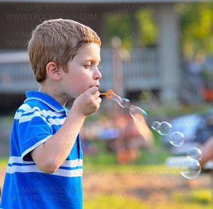 Dietrick Kaiser, seven, blows soap bubbles during Music in the Park held Thursday, June 24, in Mound Bay Park.