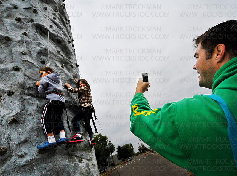 Justin Seurer, right, records his daughter Zoey's birthday party wall climb with a friend on a 30-foot tower with an auto-belay system to keep them safe, on Ninth Street during Hopkins in Motion Saturday, Sept. 17, 2011.  The climbing tower was supervised by Three Rivers Park District Outdoor Recreation staff.