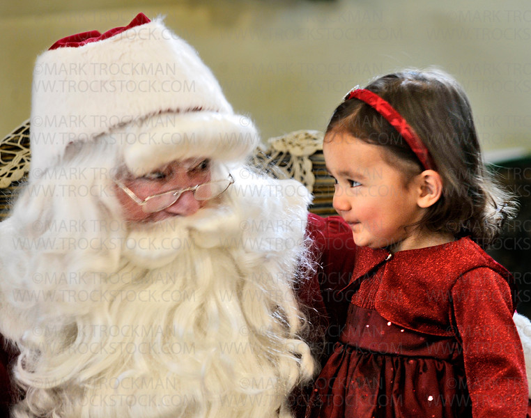 The eyes have it.  Two-year old Evelyn Anderson seems to convey a message to Santa Claus (Historical Society volunteer Floyd Wilvers) with her stare while sitting on his lap inside the Plymouth Historical Society Building at Plymouth Creek Park Sunday, Dec. 2, during the city's annual 'Old Fashioned Christmas' celebration.<br /> <br /> Visitors to the public event enjoyed refreshments, including building and making s'mores, free hayrides were offered, a story teller plied his trade, chamber singers sang, and visits with reindeer were attended, as well as the option of sitting on Santa's lap.