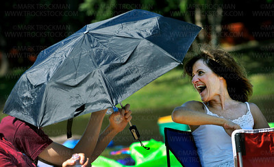 Pam Dexter, right, gets help controlling her umbrella from her son  Ryan on a windy and warm afternoon at Hilde Amphitheater Wednesday, June 29, 2011, at the 39th annual Music in Plymouth.