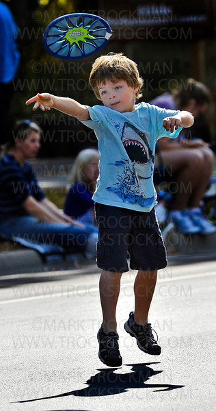 Five year old Duncan Thesingh, Maple Grove, tosses a Culvers Restaurant placemat like a Frisbee to his dad, Doug, before the start of the 2012 Plymouth on Parade Festival Saturday, Sept. 29, along Plymouth Blvd.