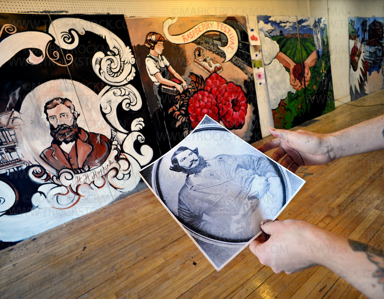Twin Cities artist Christopher Bowman compares a photograph of Harley Hopkins to his painted rendition on one of the nine panels of his artwork Wednesday, Dec. 29, in downtown Hopkins.