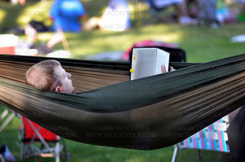 Paul Levang, Crystal, reads A Gospel Driven Life in his hammock on the Hilde Performance Center grounds during the Music in Plymouth summer festival Wednesday, June 30.  Levang and his wife Amy have been to the last five Music in Plymouth celebrations.