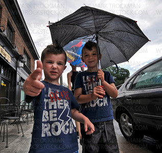 Brothers Nate, left, and Ian Crane sport matching tee-shirts and 4th of July mohawk haircuts under their Spiderman umbrella during an afternoon rain shower in downtown Excelsior Saturday.