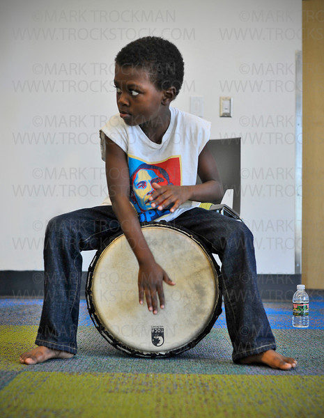 Ebrima Sarge, five, concentrates on keeping rhythm during 'Global Folk: West African Drum and Dance' program Saturday, Sept. 15, at the Plymouth Library.  <br /> <br /> Ebrima, his sister Yonci Jameson, and their mother, Kenna Cottman hosted an interactive program which included drumming, dancing, rhythm-making, and singing, free of charge.