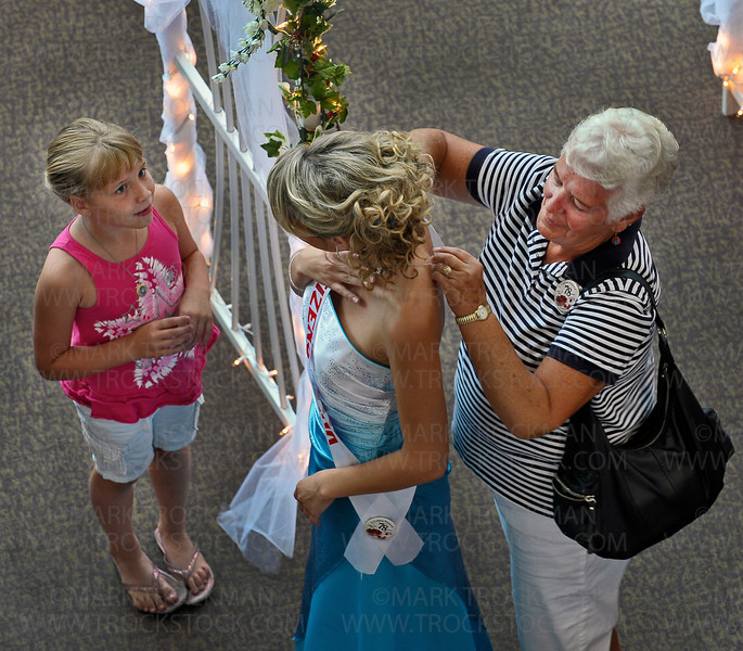 Future Raspberry Festival Princess Jimilyn Rouse, center, gets some final help from her grandmother, Donna Eddy, right, while Ariana Carlson watches her grandma attend to Jimilyn in the foyer of the Hopkins Center for the Arts Thursday, July 12.