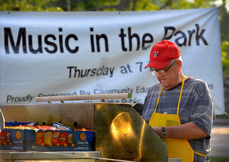 Lions Club member Bob Bittle grills hot dogs to go with the chips and candy being sold as a fundraiser for the local group Thursday, June 24, in Mound Bay Park as part of the annual Music in the Park festival.