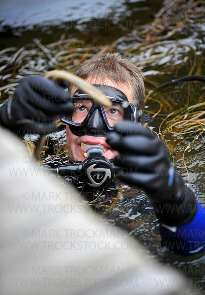 John Bergstrom, a member of the Muck Divers Connection, brings up trash from under the docks at Bayside Grill Saturday, June 12, in Excelsior.  Bergstrom and nearly 60 other SCUBA divers participated in the Lake Minnetonka Association's 9th Annual Clean Up.  Volunteer SCUBA divers collected trash and treasures from the lake in an effort to raise awareness about keeping Lake Minnetonka clean.