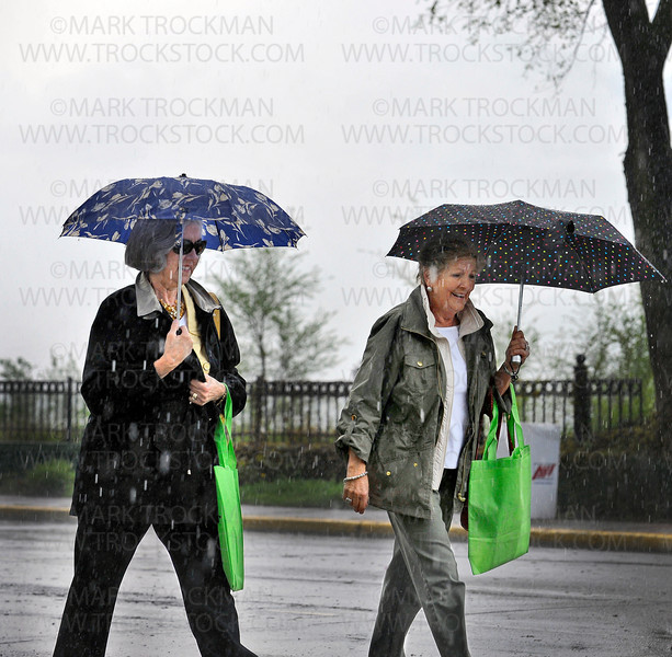 'Wayzata Art Experience' visitors make haste to covered ground as the sky opens up on Lake Street Sunday morning, May 22.  More than 100 juried artists set up tents in downtown Wayzata hoping to sell their work on a rainy, Spring weekend next to Lake Minnetonka.
