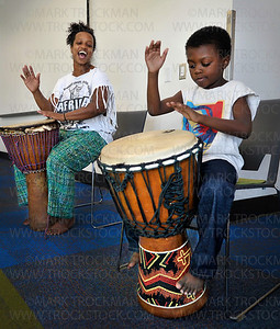 Ebrima Sarge, right, five, and his mother, Kenna Cottman, beat a rhythm during 'Global Folk: West African Drum and Dance' program Saturday, Sept. 15, at the Plymouth Library.    Cottman, and her son and daughter hosted this interactive program which included drumming, dancing, rhythm-making, and singing, free of charge.