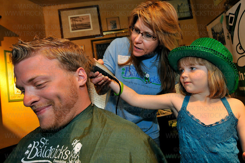 6-year-old Morgan Hagen, right, shaves Luke Ludvigson's head with guidance from Diane Blais on stage at Jake O'Connor's Public House during St. Baldrick's, a fundraiser to find a cure for children's cancer held Friday, April 24 in downtown Excelsior.