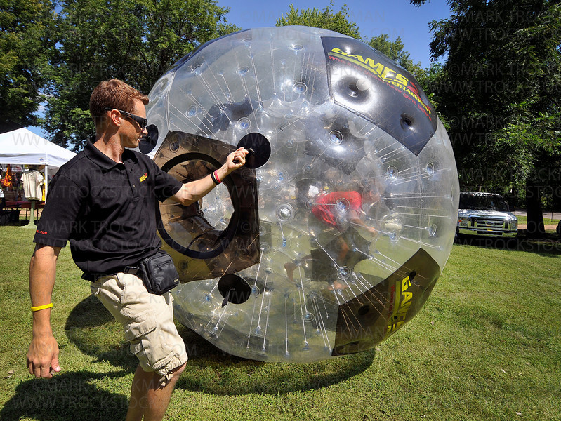 Jim Sadlovsky, owner of Games 2U Entertainment, guides his giant human hamster ball while True North, 10, spins around inside the contraption at the Church of St. George's Corn Days festival Saturday, Aug. 14, in Long Lake.
