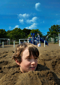 Julien Hegman, 10, is alone with his thoughts while buried up to his chin in sand at Wayzata Beach Thursday, Aug. 25, on the shore of Lake Minnetonka.  Julien was buried by his brother Mathias, 7, Miles Whealy, 10, and Eleanor Schuebel, 8, on one of the last days of summer vacation before the school year begins.