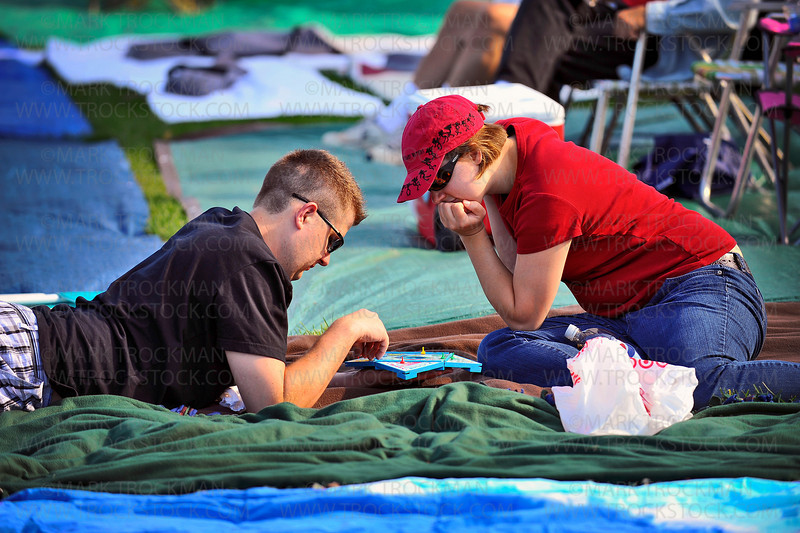 Gabrielle Grasmick, right, concentrates on a game of Sorry with her boyfriend Justin Gooch on the grounds of the Hilde Performance Center Wednesday, June 30 in Plymouth.  Many Music in Plymouth attendees bring card games and board games to occupy themselves as the Hilde Performance Center fills up with festival goers.