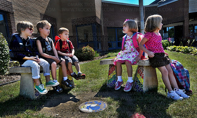 The PM Kindergarten class at Plymouth Creek Elementary School got off to a slow start due to a transportation hiccup Wednesday, Sept. 7.  Seated on mosaic-enhanced concrete benches in front of the school are, left to right, Bartlett Howe, Brandon Turner Nutter, Alex Koeller, Sydney Olsen, and Ellie R.
