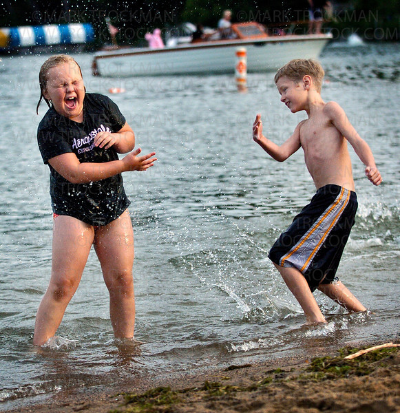 Allison Blackstone, 7,  is splashed with water by Baylee Trapp, 9,  on the beach at Mounds Bay Park Saturday, July 19 during the Spirit of the Lakes Festival.  The three day event included a Kiddie Parade, a street dance, fireworks and a food court.