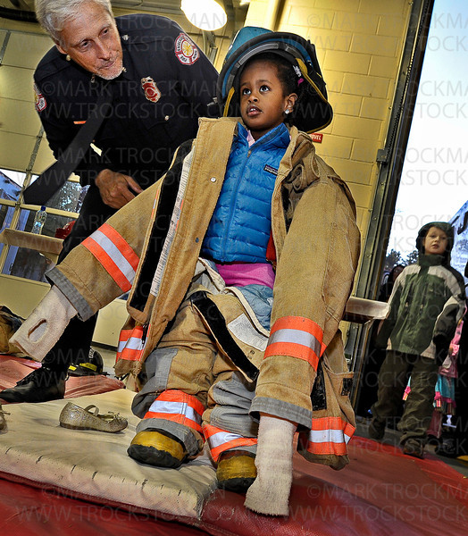 Edileh Sheedy Roach, three, gets help trying on a firefighters helmet, coat and boots with the help of fireman Bruce Duncan, at the Excelsior Fire District Station No.  1 'Excelsior Fire District Fire Prevention Open House and Safety Fair' Thursday, Oct. 11, in Shorewood.  The free, open house, had demonstrations, fire truck rides, and food during the 2 and a half hour event.