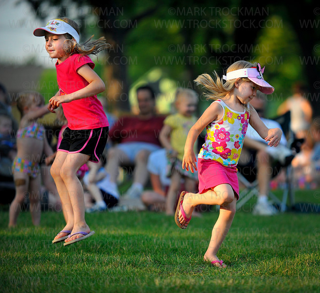 Meagan Mattson, left, six, and her four-year-old sister Kendra dance to the tunes of the band Gotta-Did-Dat in Mound Bay Park Thursday evening, June 24 during the annual Music in the Park festival on the shore of Lake Minnetonka.