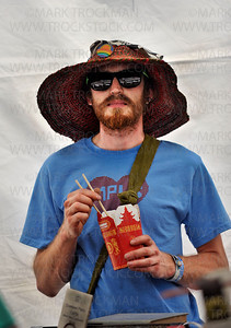 Eric Johnson, Minneapolis, digs into foreign fare in the 'Makeshift Accessories' tent. which is stocked with art his brother, Devin, creates, Sunday, June 10, 2012.  They were part of Art of the Lake,  a highly popular South Lake Minnetonka art fair in its 32nd year.