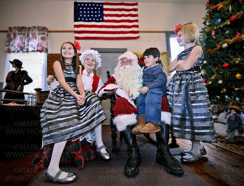 Mr. and Mrs. Claus (Floyd Wilvers and Kay Bertrand) play host to the Kaiser kids, from Plymouth, left to right, Emma, 10, Drew, 4, and Gabby, 7, inside the Plymouth Historical Building while celebrating the city's 'Old Fashioned Christmas', Sunday, Dec. 2, at Plymouth Creek Park.
