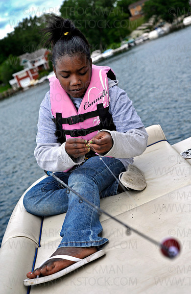 10 year old Honesty Morrow baits her hook Thursday, June 9, aboard a rental boat on St. Albans Bay on Lake Minnetonka in Excelsior.  Honesty was one of about two dozen Hopkins School District students from under privileged living situations that spent the day enjoying the Hopkins Police Department-sponsored Cops and Kids Fishing Event.