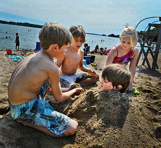 Buried at the beach.  Julien Hegman, 10, right, gets buried in the sand at Wayzata Beach by his brother Mathias, 7, left, Miles Whealy, 10, center, and their friend Eleanor Schuebel, 8, Thursday, Aug. 25, on the shore of Lake Minnetonka.