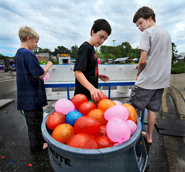 Water Wars employees, from left, Cayden Oltman, 12, Simon Gray, 12, and his big brother, Isaiah Gray, 15, fill a 30-gallon drum with water balloons for use by paying customers, who repeatedly douse one another with rubber-hose launched water bombs at the annual Minnetonka Summer Fest on the Minnetonka Civic Center Campus Saturday, June 23, 2012.