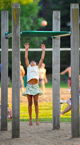 A young girl reaches for the sky in the playground area of Mound Bay Park Thursday, June 24, during the annual summer festival Music in the Park on the shore of Lake Minnetonka.
