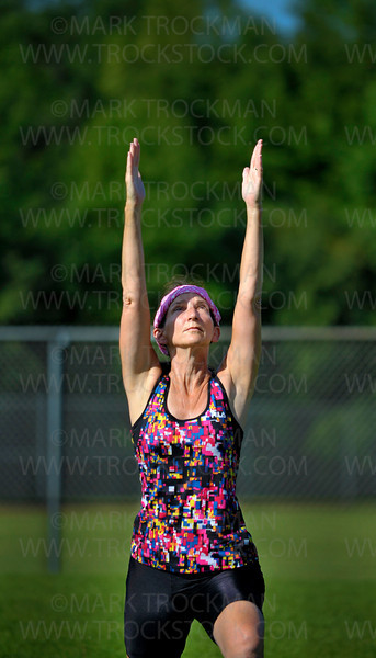 "Holy Yoga participant Jane Revsbech, Chanhassen, assumes a Warrior One pose at Freeman Park, Friday, July 29, in Shoreview.  Instructor Bethany Connelly believes, ""Holy Yoga attracts a variety of people, and that's what makes it beautiful. If you're a first timer, that's okay."""