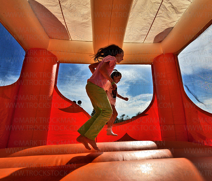 Mikayla Murray, left, Monticello, and Erica Kazin, Maple Plain,  jump around inside a huge inflated orange fun house at the Loretto Lions Park during the 13th annual Loretto Fun Fest, held Saturday, Sept. 15, in the West Metro city.