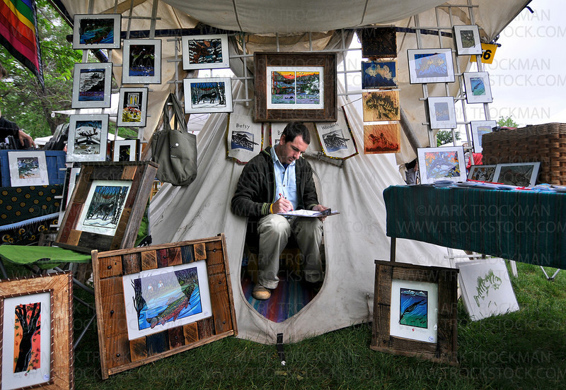 Phil in a hole.  Phil Bowen takes stock of his mother Betsy's woodcut art in their tipi at Art on the Lake in Excelsior Commons Sunday, June 13.  Betsy Bowen, Grand Marais, has sold her unique woodcut artwork, books, cards and framed pieces at the art fair since the early 1990's.
