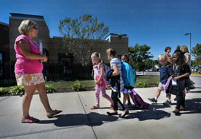 PM Kindergarten teacher Jane Johnson leads several of her students into the building at Plymouth Creek Elementary Wednesday, Sept, 7, 2011.  The first day of school for the PM kindergarten students and teachers had a slow start due to a transportation hiccup.