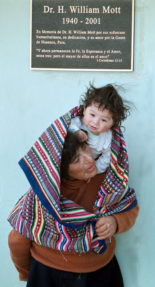 Photo by Bill Schaefer<br /> A mother and her infant wait under a memorial plaque dedicted to Pocatellan Dr. William Mott at the DeClercq Clinic in Huanuco.