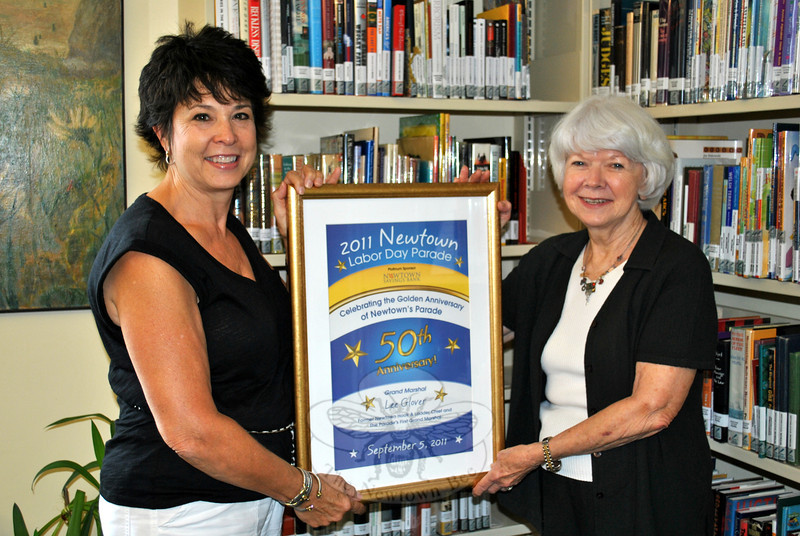 Newtown Labor Day Parade Committee President Beth Caldwell, left, presents C.H. Booth reference librarian Beryl Harrison with a framed poster print of the 2011 parade program, Thursday, August 23, to add to its collection of posters from previous years' parades. (Crevier photo)