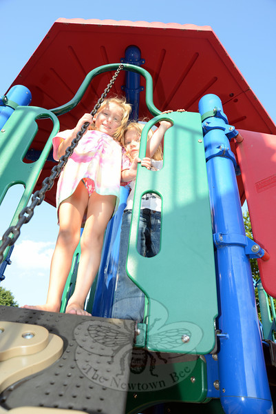 Sarah Kirkman, left, and Ilse Popovic squeeze together at the top of a steep slope back to the ground at the Treadwell playground Wednesday, August 22. (Bobowick photo)