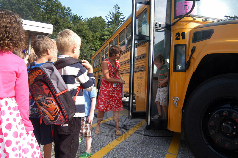 Sandy Hook School Principal Dawn Hochsprung, center, greeted kindergarten students as they arrived on Friday, August 24, after being picked up by their buses for a prerun experience. Some parents also drove their students to the school for the event. After being dropped off, the kindergarteners were also given the chance to become familiar with the school and their classrooms. Kindergarten bus runs were held in advance of the school year's start at each of the elementary schools. (Hallabeck photo)