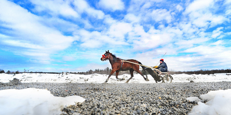 """Clifford Chase of Wilton exercises his three year old trotter around a muddy Farmington Fairgrounds that still has a ring of snow around the edges Wednesday morning.  """"We do this every day mud or not.""""  said the energetic sulky driver, covered head to toe in mud.  He was one of several racers out on the track preparing for the first day of harness racing at Scarborough Downs next Saturday, April 2."""