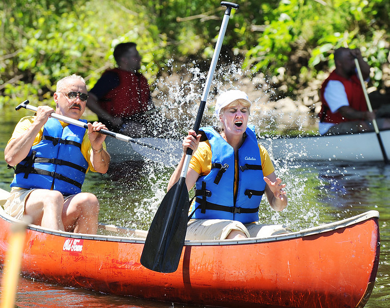 "Bob Veilleux of Lewiston, splashes his wife Diane after crossing the finish line of the 13th Annual Chief Worumbo Androscoggin River Race in Lisbon Sunday morning.  ""It was a safety situation with the heat and all"" Bob said.  According to his wife Diane, the best part was that they finished ahead of their three daughters.  ""They will never hear the end of it.""  Nearly 100 compeditors enjoyed the perfect weather conditions that started at the boat launch on Route 136 in Durham, finishing 6 miles later under Route 196 in Durham where the Sabattus River meets the Androscoggin. The race is part of the weekend long Moxie Festival.   For dozens more photos from the race, visit  <a href=""http://www.sunjournal.com"">http://www.sunjournal.com</a>."