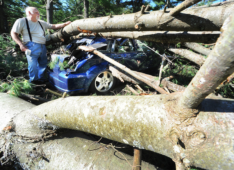 Jim Dion surveys the damage to his 2 year old car that was destroyed when sevearl trees came crashing down on it Sunday afternoon in his driveway on Park Street in Sabattus during Tropical Storm Irene.  Monday afternoon he and his neighbors were still without power after other falling trees snapped a utility pole just down the street.